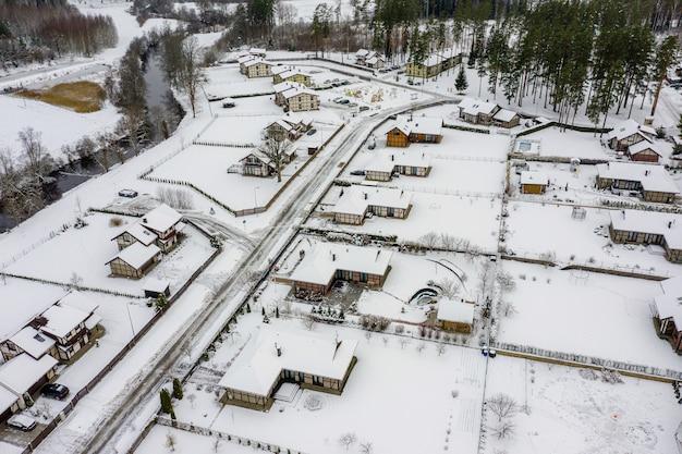 눈이 덮여 주택과 도로가있는 겨울 마을의 상위 뷰, 위에서보기