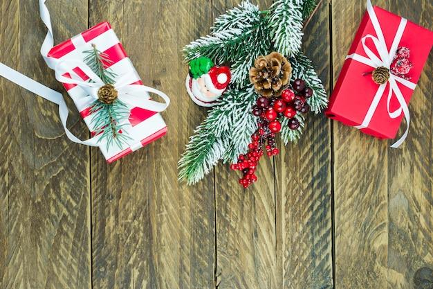 新年の贈り物、トウヒの枝とベリー、サンタの置物と木製の村のテーブルの上面図。上面図。