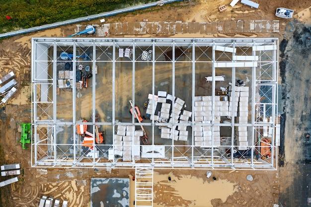 Вид сверху на рабочую зону и большой стальной каркас большого коммерческого здания. строительство склада