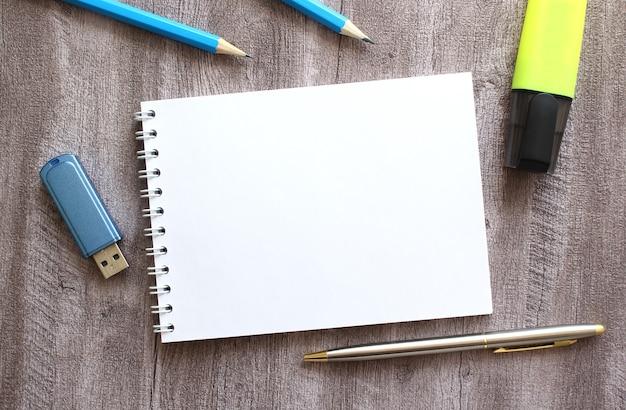 작업 공간의 상위 뷰입니다. 회색 나무 테이블에 텍스트, 펜, 연필, usb 플래시 드라이브를 위한 빈 공간이 있는 메모장. 비즈니스 개념입니다.