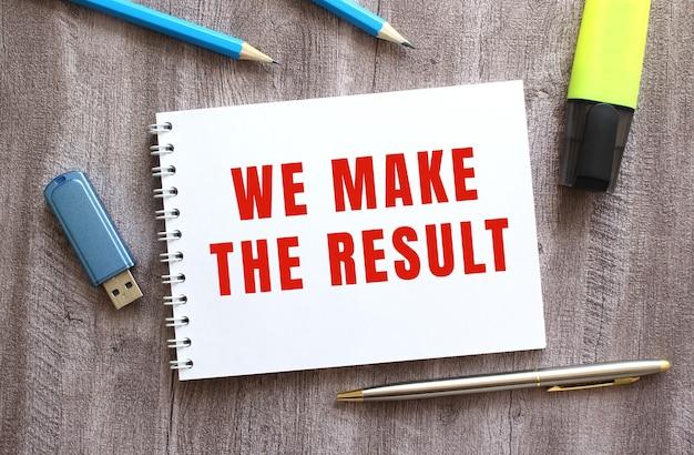 작업 공간의 상위 뷰입니다. 회색 나무 테이블에 we make the result 텍스트, 펜, 연필, 플래시 드라이브가 있는 메모장.