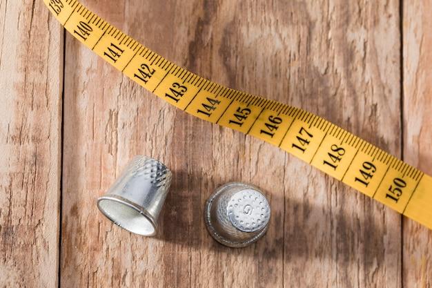 木製の表面に測定テープと指ぬきのトップビュー