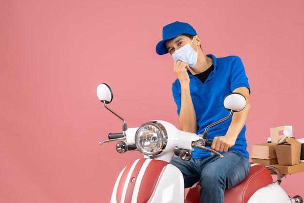 Вид сверху думающего курьера в медицинской маске в шляпе, сидящего на скутере на пастельном персике