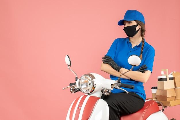 医療用マスクと手袋を着た思いやりのある宅配便の女性がスクーターに座ってパステルピーチの注文を配達するトップビュー