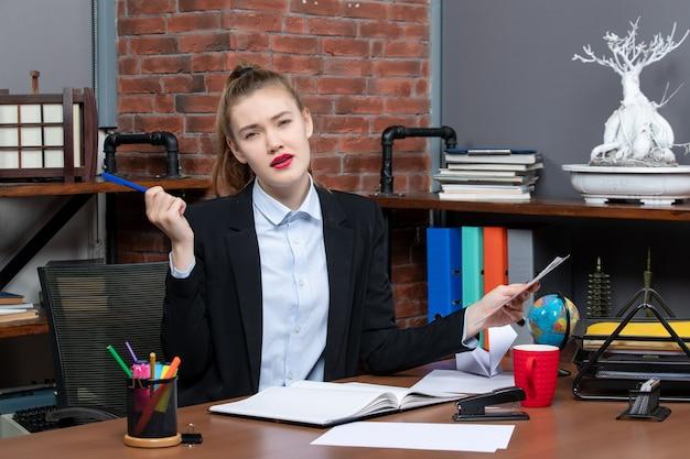 テーブルに座って、オフィスでドキュメントの青い色のペンを保持している思いやりのある女性の上面図