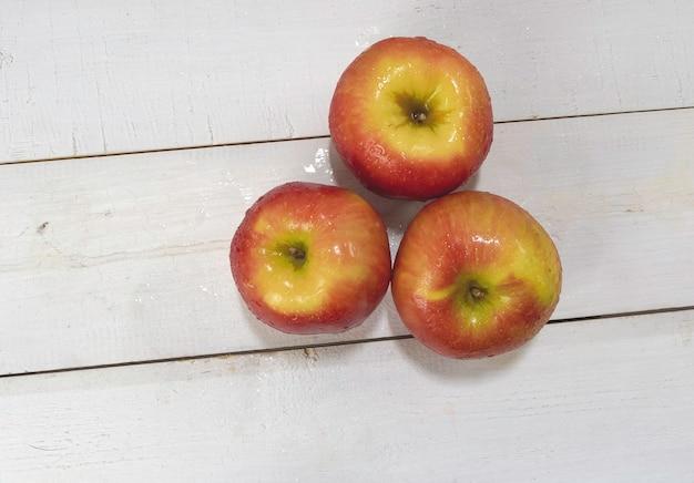 周りの水滴で濡れた3つのリンゴの上面図、木の板を置き、周りのぼやけた光