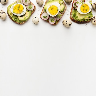 Вид сверху на три бутерброда с яйцом и авокадо с копией пространства