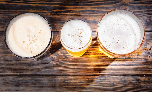 木製の机の上に明るい、フィルタリングされていない、暗いビールと3つのグラスの上面図。食品および飲料の概念