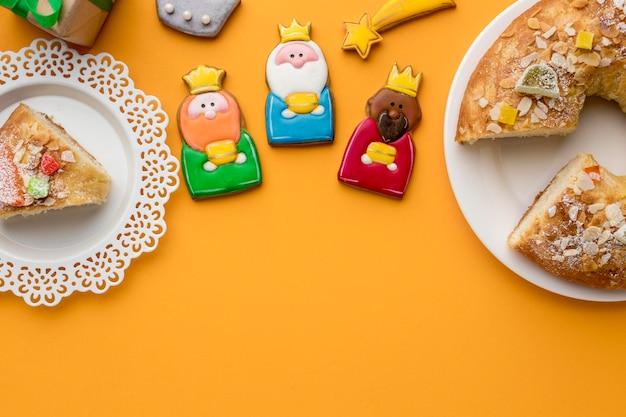 Вид сверху трех королей с коронами на день крещения и десерт на тарелке