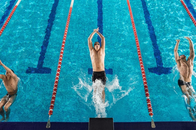 Вид сверху трех пловцов мужского пола
