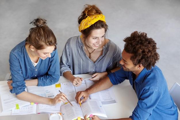 本やコピーブックに囲まれたテーブルに座っている3人の学生の平面図。興味深く何かについて話し合って、幸せな表情を見せています。ブレーンストーミング、チームワーク、教育のコンセプト