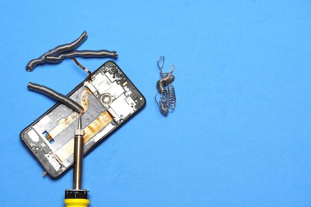 깨진 모바일 스마트폰 수리 개념 평면에 있는 주석 및 주석 납땜 인두의 상위 뷰