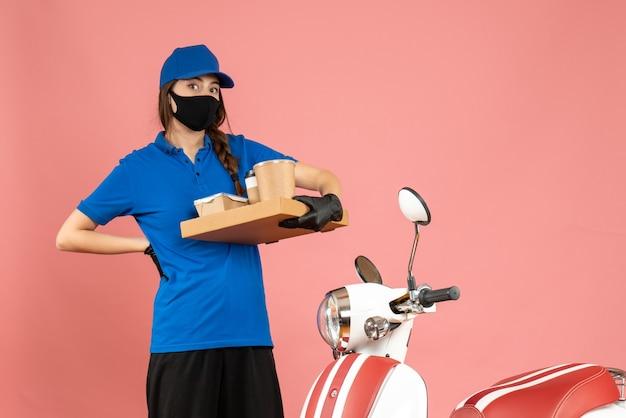 パステル ピーチ色のコーヒーの小さなケーキを保持しているオートバイの横に立っている医療マスク手袋を着て疲れた宅配便の女の子のトップ ビュー