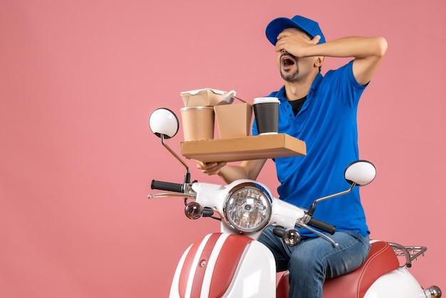 パステル ピーチのスクーターに座っている帽子をかぶった疲れた宅配便のトップ ビュー