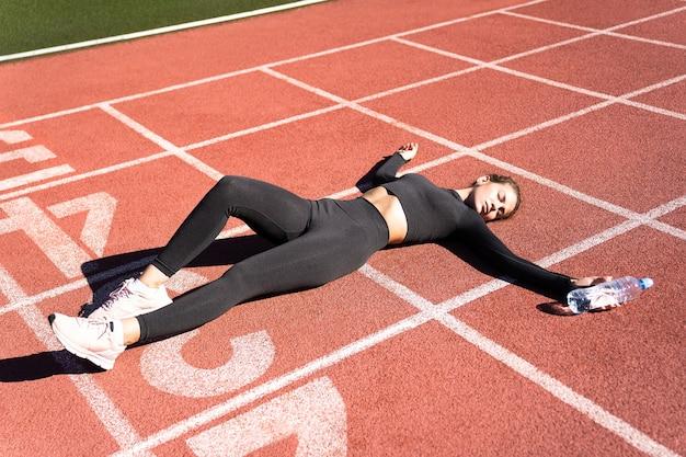 운동 후 휴식을 취하거나 러닝 머신 고무 경기장에서 실행하는 운동복에 피곤한 맞는 여자의 상위 뷰