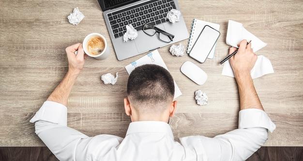 피곤하고 과로한 사업가, 회사원, 노트북, 커피, 서류를 들고 책상에 누워 있는 모습.
