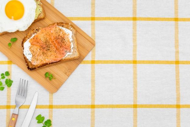 Вид сверху тост на разделочную доску с яйцом и столовыми приборами