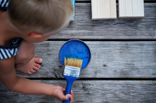 Вид сверху на малыша, окунающего кисть в ярко-синий цвет, чтобы нарисовать деревянные доски.