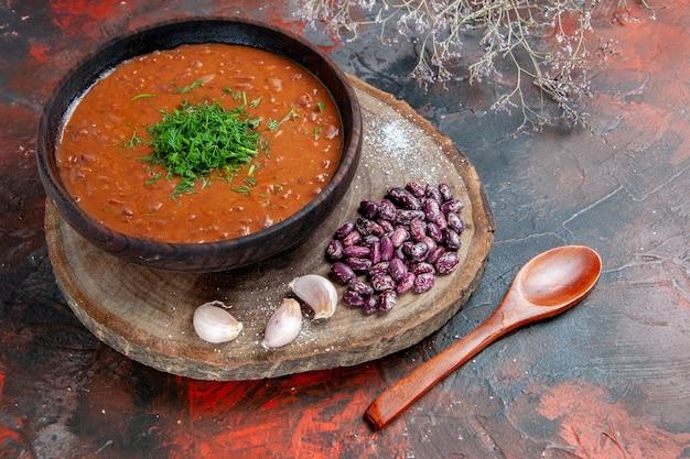 木製のまな板にトマトスープ豆にんにくとミックスカラーの背景にスプーンの上面図