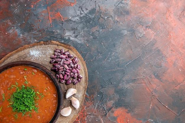 ミックスカラーの背景の木製まな板にトマトスープ豆にんにくの上面図