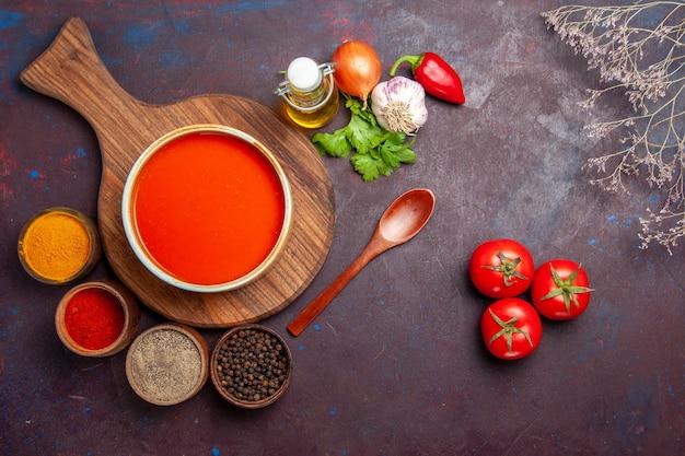 黒いテーブルに調味料とトマトスープの上面図