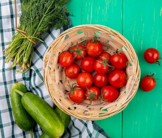 격자 무늬 천과 녹색 표면에 바구니와 오이 딜에 토마토의 상위 뷰