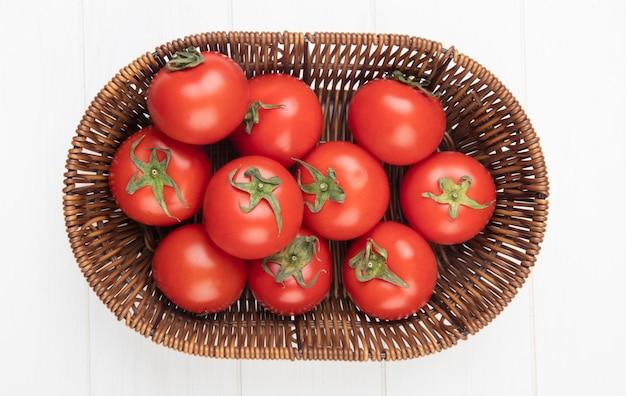 Вид сверху помидоры в корзине на белой поверхности