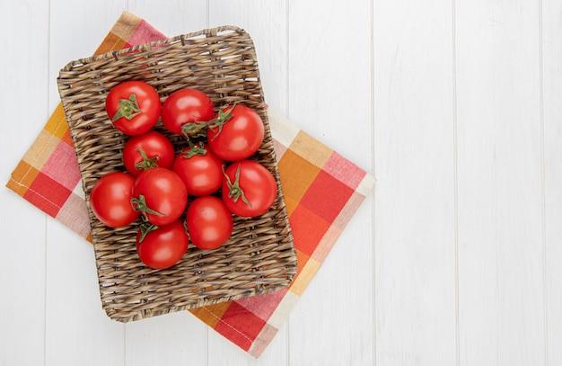 Вид сверху помидоры в корзине на клетчатой ткани на левой стороне и деревянной поверхности с копией пространства