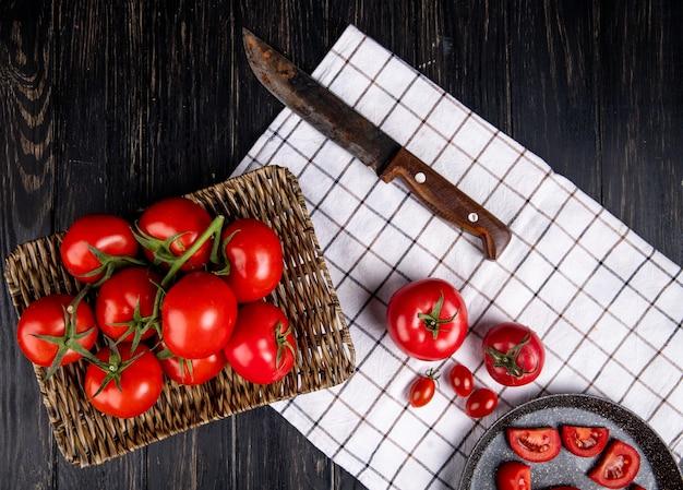 Вид сверху помидоры в корзине с другими на ткани и ножом на деревянной поверхности