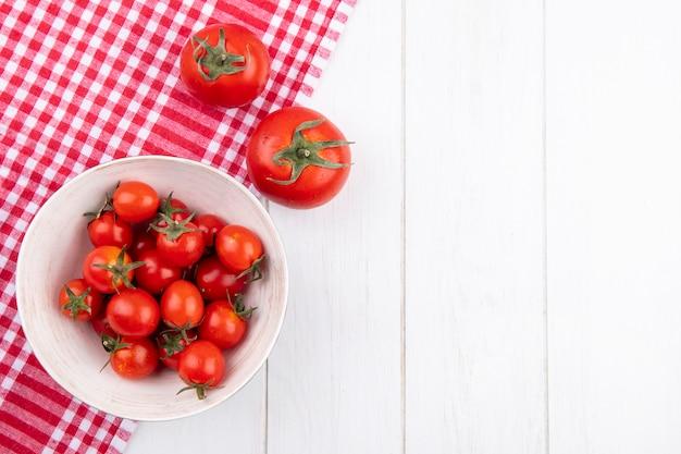 Вид сверху помидоры в миску на клетчатой ткани и на деревянной поверхности