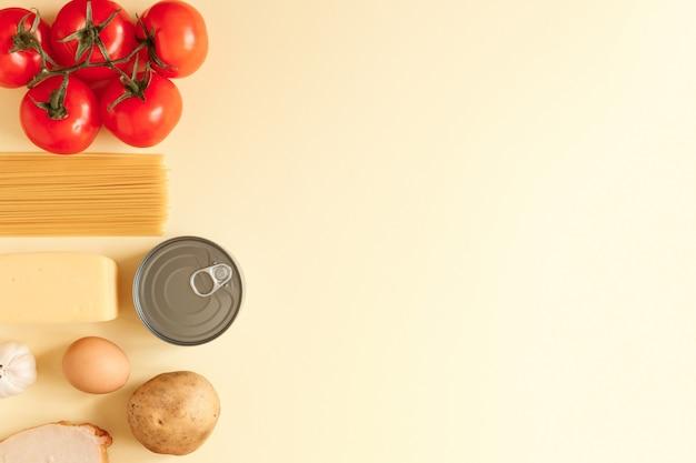 복사 공간이 밝은 노란색 배경에 토마토, 참치 캔, 감자 등의 상위 뷰