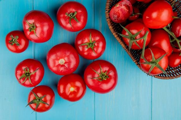 Вид сверху помидоры с корзиной помидоров на синей поверхности