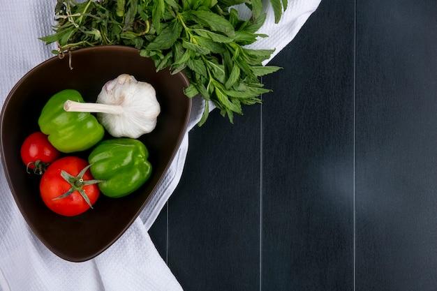 Вид сверху помидоров с чесноком и болгарским перцем в миске на белом полотенце с мятой на черной поверхности