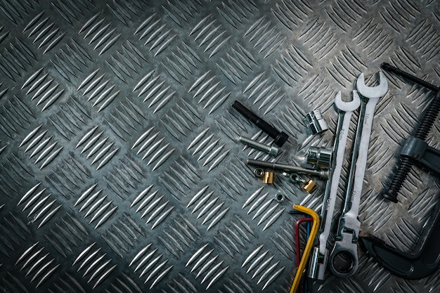 Взгляд сверху инструментов на промышленной плите контролера металла. металлическая шахматная доска для противоскольжения. гайка, болты и шестигранный ключ на металлическом листовом полу. серебряная шишка