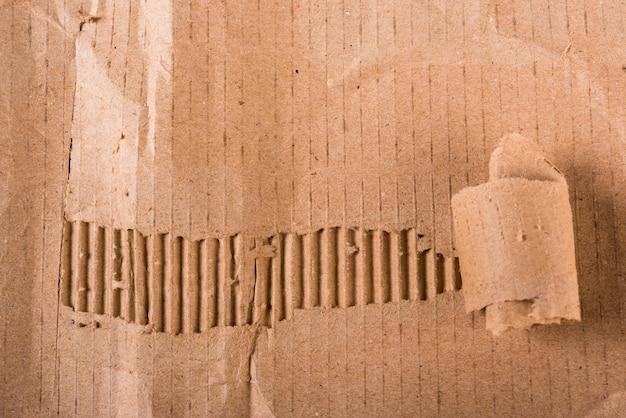 Вид сверху на рваные края гофрированного коричневого картона на листе бумаги текстуры или фона