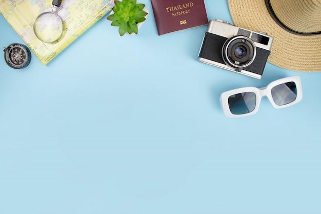 青色の背景にフィルムカメラ、地図、パステル、帽子、サングラス、スマートフォンと観光アクセサリーの平面図。旅行のコンセプト