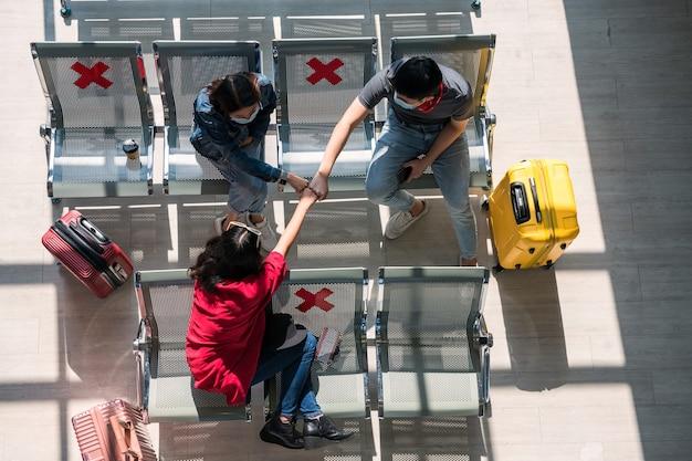 空港ターミナルの座席エリアでフェイスマスクフィストバンプと観光客の上面図