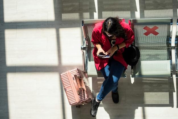 얼굴 마스크와 관광 여자의 상위 뷰는 수하물 근처 좌석 공간에 앉아 공항 터미널에서 전화를 사용합니다. 코로나 19 예방을위한 새로운 일반 여행 라이프 스타일