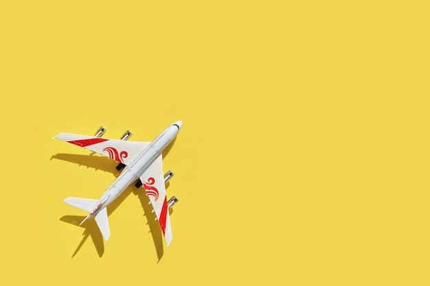 복사 공간이 있는 노란색 배경에 있는 장난감 비행기의 상위 뷰