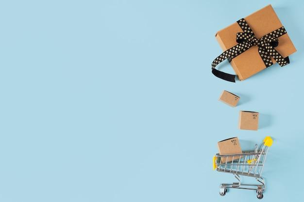 Вид сверху игрушечной тележки для покупок с коробками и подарком на синем фоне, копируя пространство для текста или дизайна