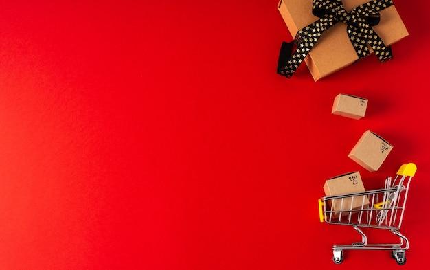 Взгляд сверху тележки игрушки с коробками и подарком на красной предпосылке. скопируйте место для текста или дизайна