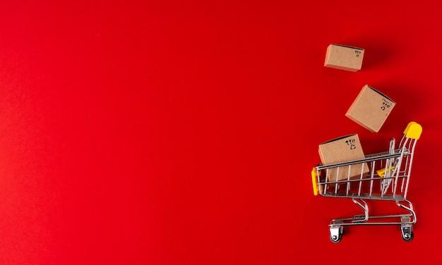 Вид сверху игрушечной тележки с коробками и подарком на красном фоне