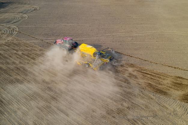 Взгляд сверху трактора засаживая семя мозоли в поле, фотография трутня взгляда высокого угла