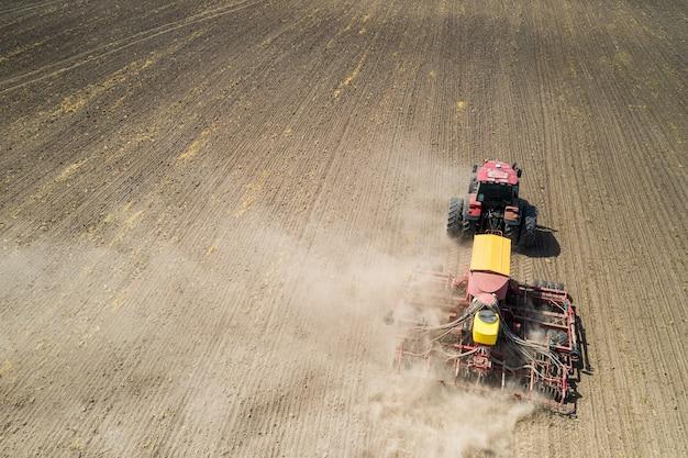 Вид сверху трактора, высаживающего семена кукурузы в поле, фотография с дронов под высоким углом