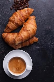 ホットコーヒーと伝統的なクロワッサンの上面図。ゴールデンクロワッサン。