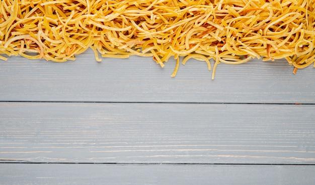 Вид сверху традиционные домашние итальянские сырые макароны с копией пространства на деревенском фоне