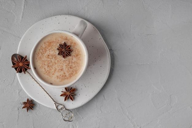Вид сверху традиционного индийского чая масала со специями в чашке на сером столе, место для текста. напиток для повышения органического иммунитета