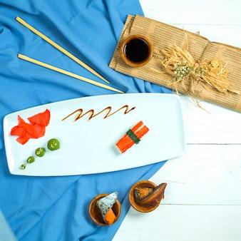 Вид сверху традиционных японских суши нигири с тунцом, подается с соевым соусом и имбирем с васаби на синем и белом