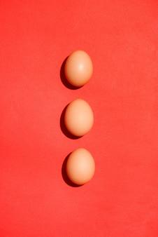 赤い背景の上の伝統的な赤いイースターエッグの上面図。