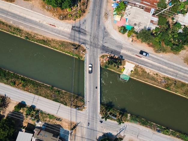 Вид сверху движения на перекрестке дороги через мост на канале в сельской местности